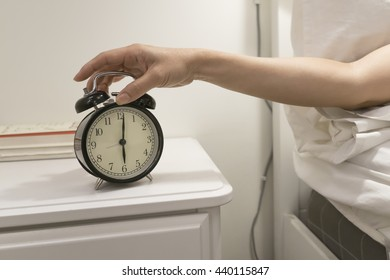 Hand reaching out for alarm clock.