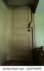 Hand reaching out from behind an old door. Low angle. Horor.