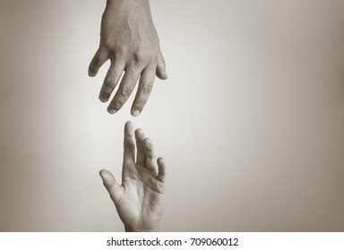 Hand reaching out to help another. People helping each other.