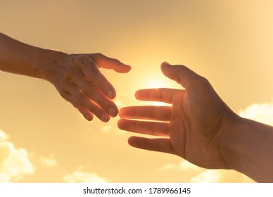 Hand reaching out to help hand on sky background. Giving a helping hand concept.