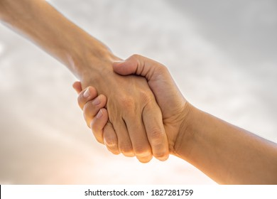 Hand reaching out to help support another.