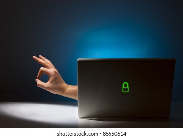 A hand is reaching out from a laptop giving the OK hand signal.