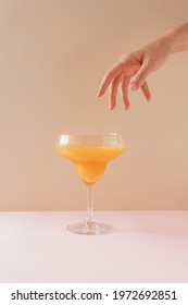 Hand reaching out to orange drink in cocktail glass against pastel background. Minimal summer concept.