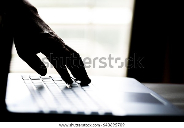 A hand reaching out through a laptop computer and signifying a cybercrime in internet theft while using online, Payment Security Concept. Hacked in Black