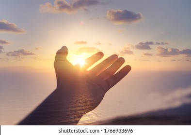 Hand reaching out to touch the warm rays of sunshine. Mind, body, spirit, and freedom in nature concept