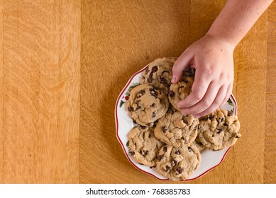 Hand reaching for a plate of cookies.