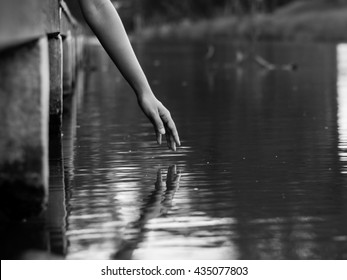 A hand reaching to water surface with reflection