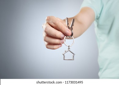 Hand of a real estate agent holding house keys on grey background
