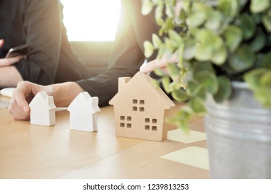 Hand of Realestat Estate Agent choose type of home mock-up to preset the customer. Financial adviser working with client.Architect builder planning the house at the table with mock up.