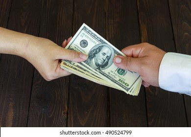 Hand receiving money from the businessman. Businessman to pay off debts .