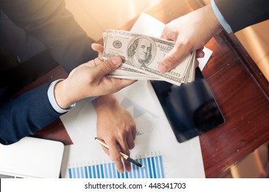 Hand receiving money, US dollars, from business man on office desk in office