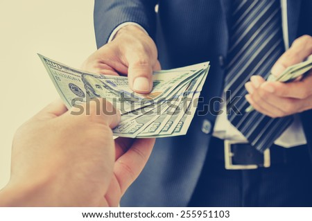 Hand receiving money, US dollars,  from business man - vintage (retro) style color effect