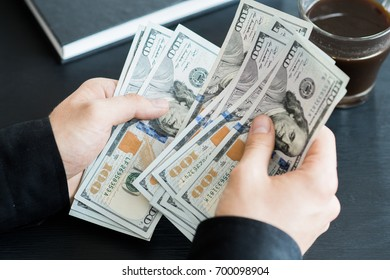 hand recount dollars. the man counts the money. new hundred-dollar bills