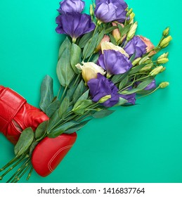 hand in a red boxing glove holding a bouquet of flowers Eustoma Lisianthus on a green background