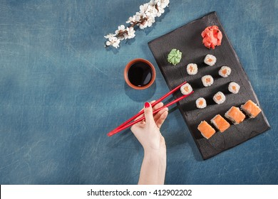 Hand with red chopsticks on sushi set with soy sauce, wasabi, sakura and ginger on black cooking desk. Flat lay, top view.