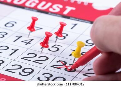 Hand with a Red Felt-tip Pen Marking a Date in Calendar