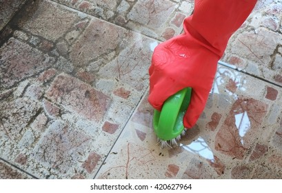Hand in red glove cleaning tile floor
