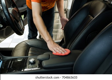 Hand with red microfiber sponge waxing interior car