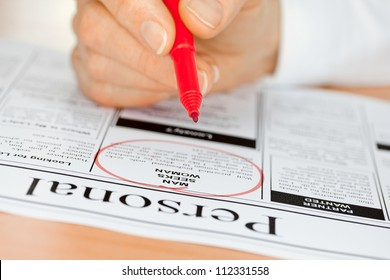 Hand with Red pen Finding a Personal Ad in the Newspaper