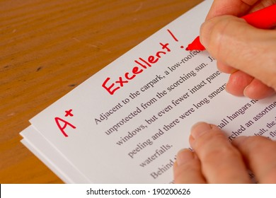 Hand with Red Pen Grading Papers with Excellent - Success concept in education industry