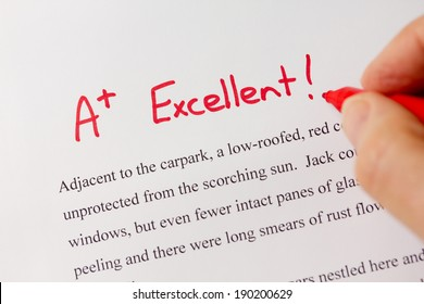Hand with Red Pen Grading Successful Essay with Excellent - Success concept in education industry