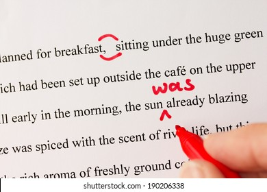Hand with red pen proofreading a novel