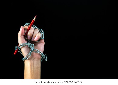 Hand with red pencil tied with fetters, depicting the idea of freedom of the press or freedom of expression on dark background in low key. world press freedom day concept.