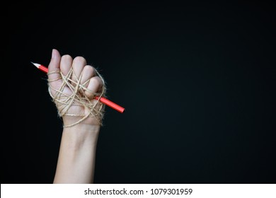 Hand with red pencil tied with rope, depicting the idea of freedom of the press or freedom of expression on dark background in low key. world press freedom day concept.