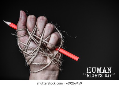 Hand with red pencil tied with rope, depicting the idea of freedom of the press or freedom of expression on dark background in low key. International human rights day concept.