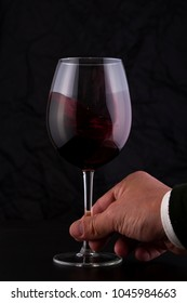 Hand with a Red Wine Glass in Motion in a Black Background