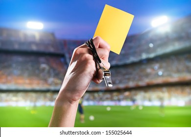 Hand of referee with yellow card and whistle in the soccer stadium.
