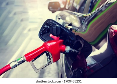 Hand refilling the black car with fuel at the gas station. Oil and gas energy.