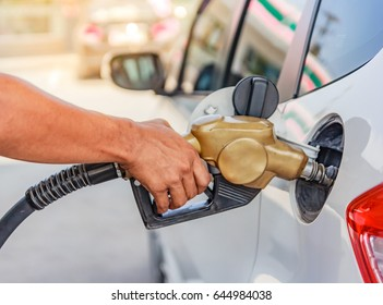 Hand refilling the car with fuel at the gasoline station