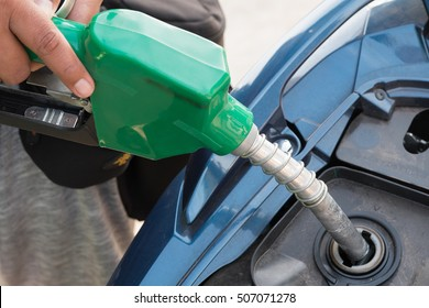 Hand refilling the car with fuel.Close-up of a mens hand refilling the car with a gas