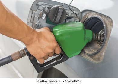 hand refilling the car with green fuel nozzle on petrol filling a  station