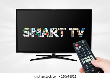 Hand with remote control aiming modern Smart TV device