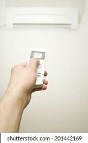 Hand with remote control and air conditioner