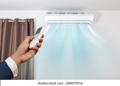 Hand with remote control directed and air conditioner on wall background