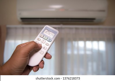 Hand with remote control directed on the conditioner temperature