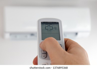 Hand with remote control directed on air conditioner. Air conditioner inside the room with man operating remote controller.
