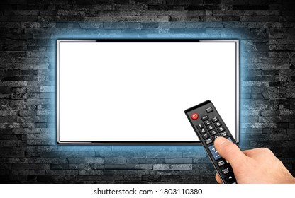 hand with remote on empty black flat tv screen display with copy space isolated white background. television wall mounted on dark slate stone wall glowing blue LED background. Multimedia streaming