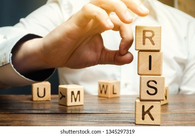 Hand removes blocks with the word Risk. The concept of reducing possible risks. Insurance, stability support. Legal protection of business interests. Favorable investment climate.