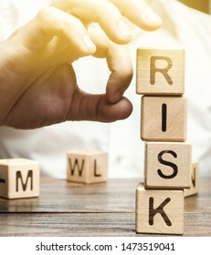 Hand removes blocks with the word Risk. The concept of reducing possible risks. Insurance, stability support. Financial pillow. Legal protection of business interests. Favorable investment climate.