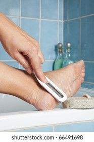 Hand removing callus from feet using pumice stone and file