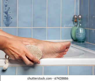 Hand removing callus from feet using pumice stone