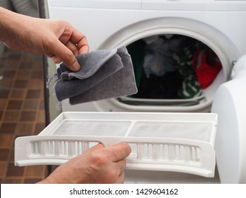 Woman's hand removing lint from fluff filter of the tumble dryer on blurred background of clothes dryer with washed clothing. Laundry processes, Cleaning and care concept. (close up, selective focus)