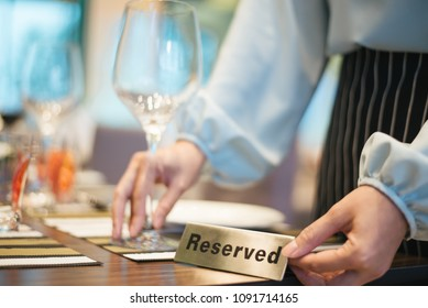 Hand with Reserved Table. Elegant Restaurant Table Setting Service for Reception with Reserved Card.