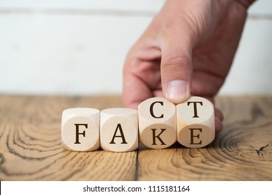 "hand reveals that a ""fact"" is a ""fake"" by flipping two cubes"