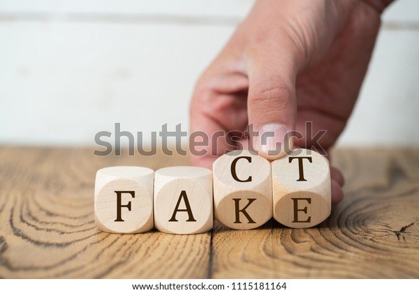 """hand reveals that a """"fact"""" is a """"fake"""" by flipping two cubes"""