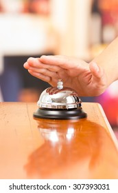 hand ringing hotel bell in reception desk close up selective focus
